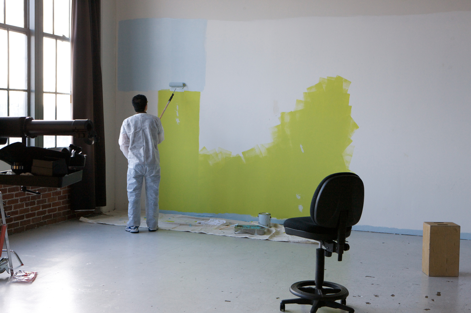 First camera assistant, Michael, at Peter Belanger's studio painting the backdrop wall for the next's day's shoot.