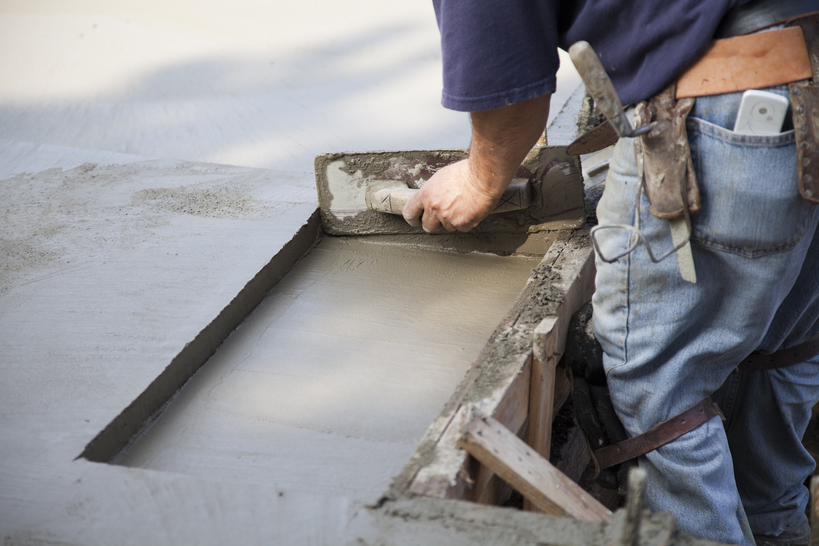 Using a hand trowel to tidy the edge where a door tread will rest flush with the concrete floor.