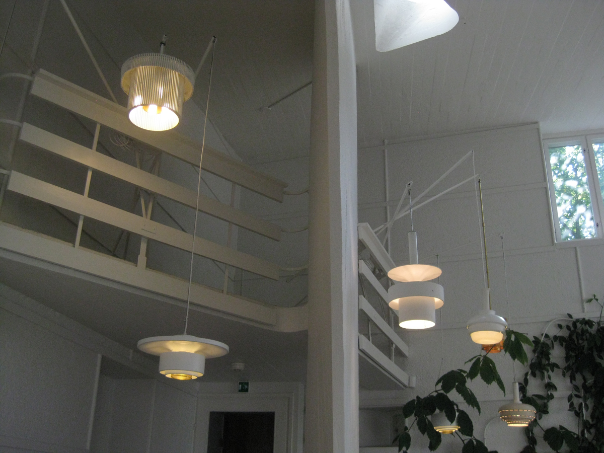 Like fishing lines dangling off a pier, in Aalto's expansive office various lighting experiments hang from a small mezzanine. The pendant designs were generally under consideration for large public buildings, and hung from this height Aalto and his staff