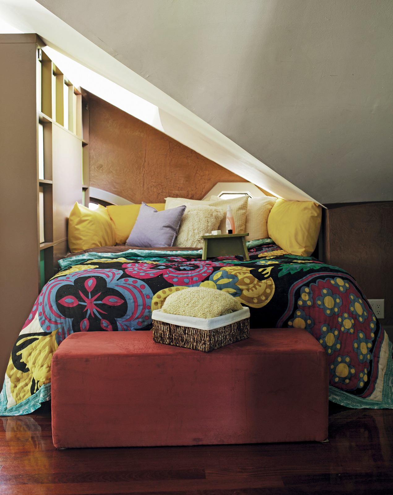 This top floor loft space in Atlanta has uneven ceilings and no walls, so Schuneman sectioned off a nook for her bed using a tall bookcase. Reprinted from The First Apartment Book by Kyle Schuneman. Copyright © 2012.  Published by Clarkson Potter, a divis
