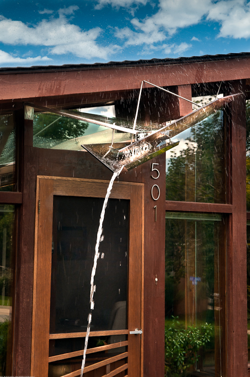 This close-up view really gives you a sense of the awning's purpose: The four glass planes and metal hardware affixed to the facade divert rainwater away from the front door and out into a planter. What's more, the awning was engineered to handle Boulder'