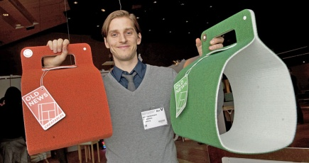 Erik holding up two Old News newspaper holders in a photo by Jonas Ekstromer.