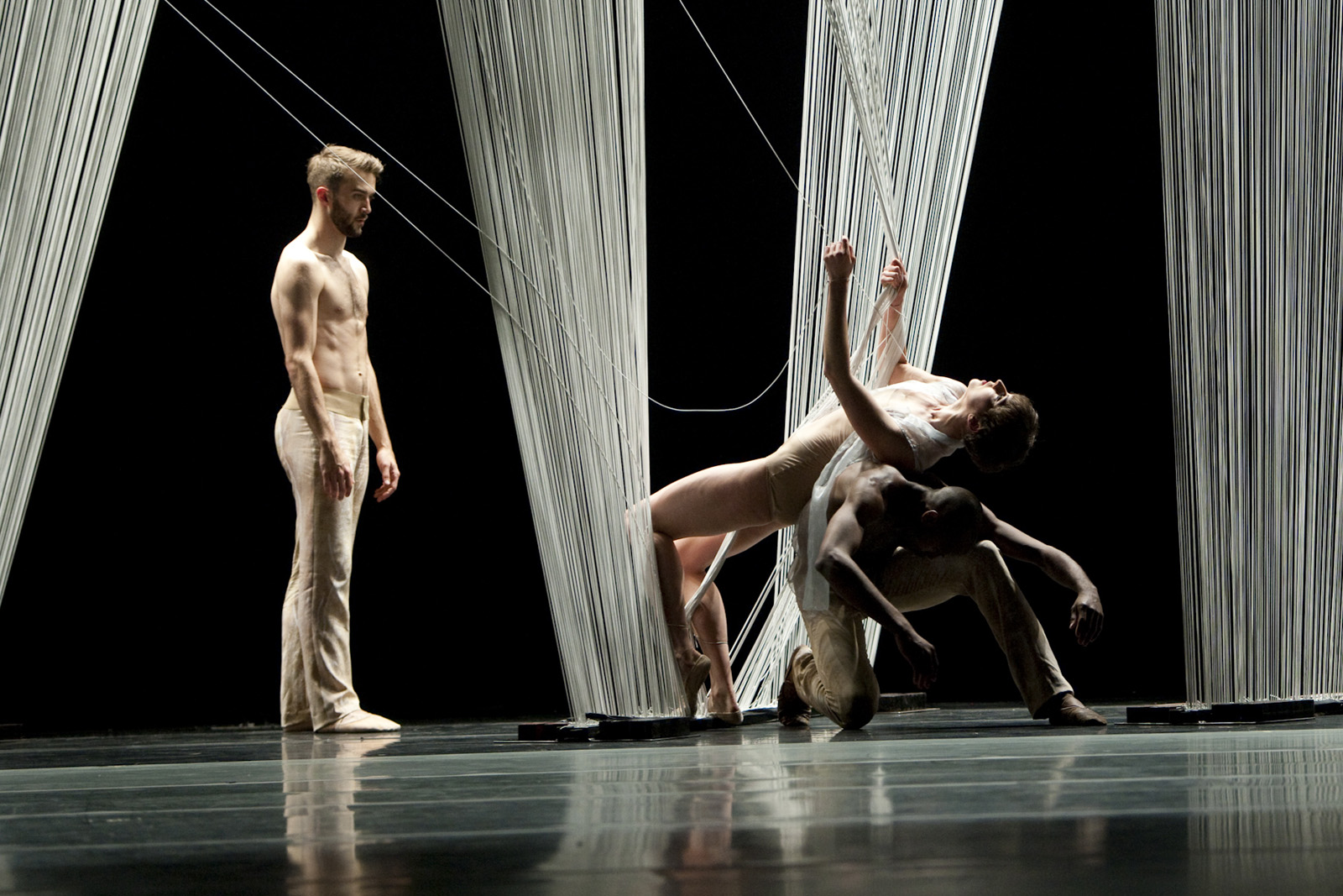 Haas designed two different sets for the two acts of the ballet. The first was a long curtain of shimmering, gossamer elastic cords. Almost immediately the dancers created three triangular gaps in the curtain, setting up one of the central activities of t