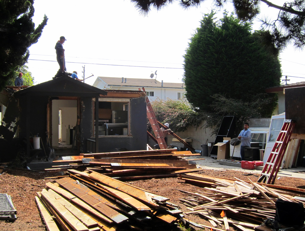 Windows, doors and cabinets are stacked on the driveway. Lumber is sorted into piles according to size and type. The large front yard acts as a staging area.