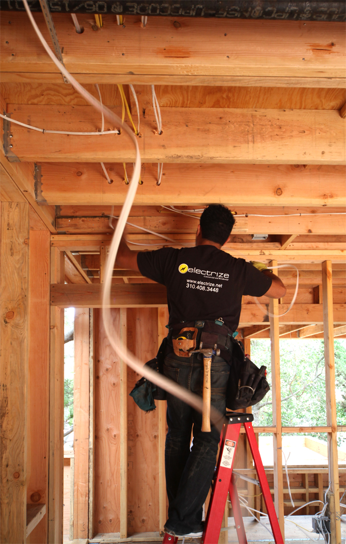 "Joe works out routes for wiring that do not conflict with plumbing. It can get crowded in the wall and roof cavities. This stage of the project is known as ""rough electrical."" Once the drywall is installed Joe will come back and install the ""finished elec"