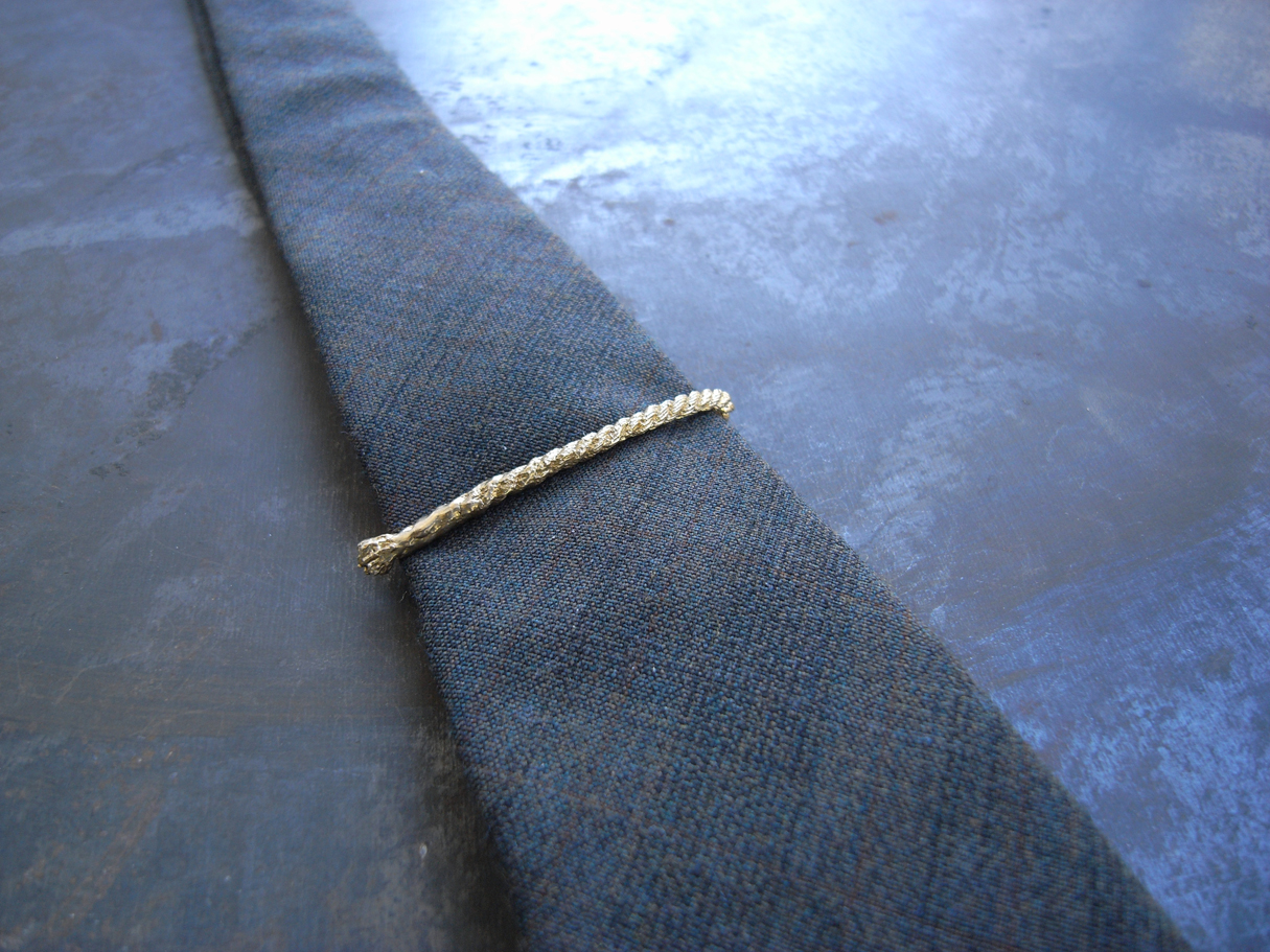 This tie clip is made of cast string and serves as a rather homespun antidote to all those mad men running around.