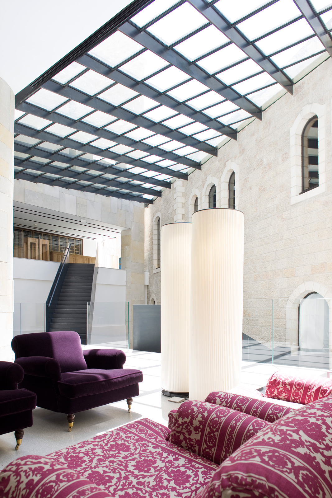 As conceived by Safdie, a pristine ceiling of glass and steel tilts to meet Mamilla Hotel's grand structure of Jerusalem stone. Sunlight pours through, bathing the interiors with warmth and brightness. Eggplant-hued lounges cozy up the sitting area as wel