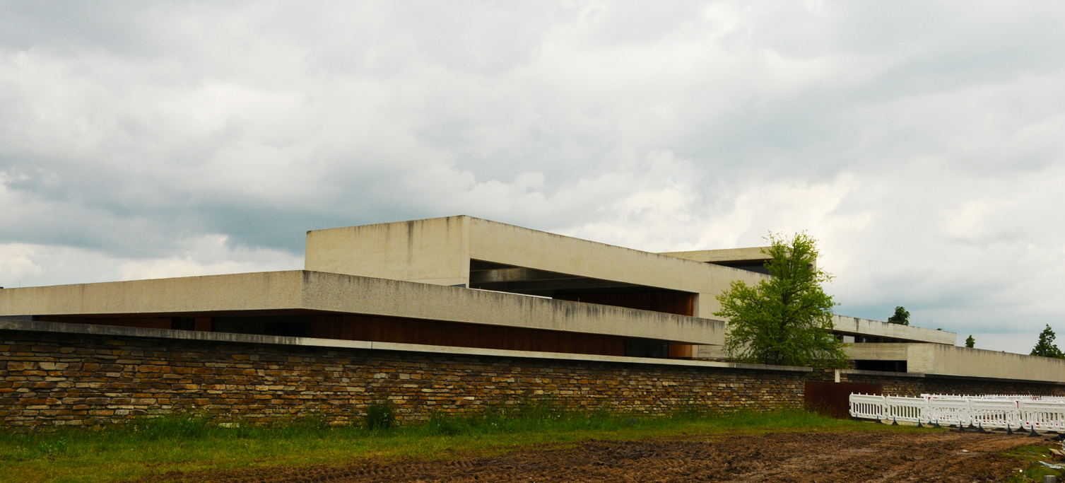 From afar, the Mortuary at Munich-Riem seems foreboding, suggesting the standing remnants of a bygone communist design. The rough exterior of untreated concrete is set in cantilever, creating dark horizontal crevices along the facade.