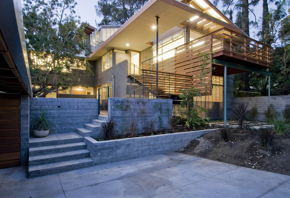 Up the drive to a two-car cover and parking area, a set of concrete stairs leads to a central patio. Retaining walls are optimized with cast-concrete seams and planting beds filled with native grasses, lending texture and interest. It's another flight up