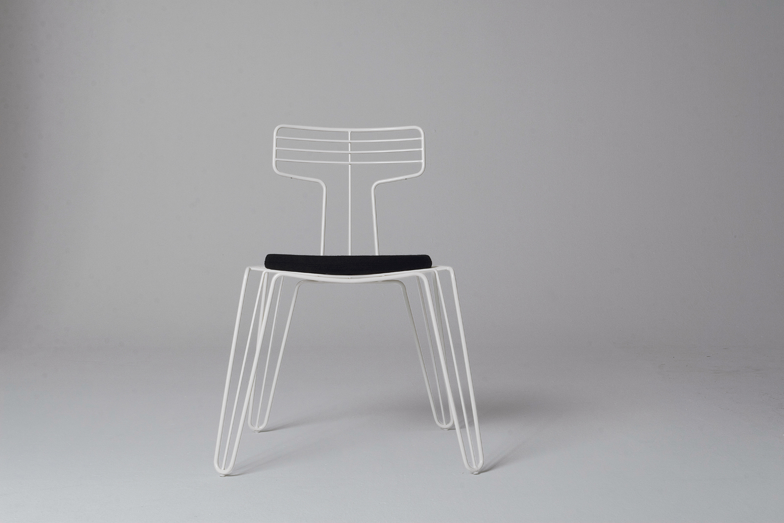 A dining chair from Tom Dixon's Wire series, which includes a coat rack and stand.