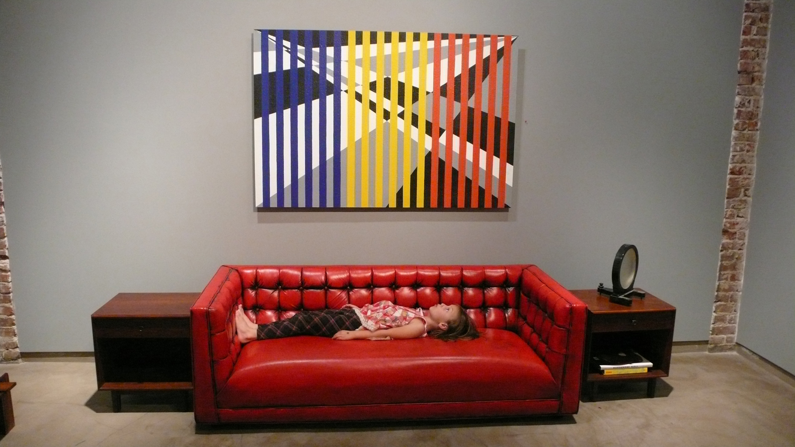 A young visitor on a Milo Baughman tufted sofa in red leather with black accents, beneath <i>Crossroads</i>, a 2000 acrylic-on-Masonite painting by 1960s furniture designer Arthur Ellsworth, which sold on the gallery's opening night.