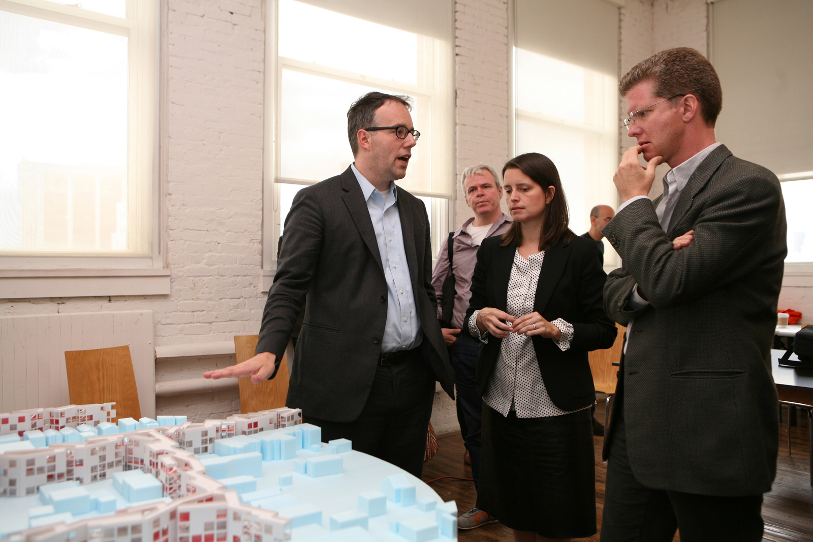 U.S. Secretary of Housing and Urban Development Shaun Donovan (right) discusses MOS's proposal with Michael Merideth and Hilary Sample.