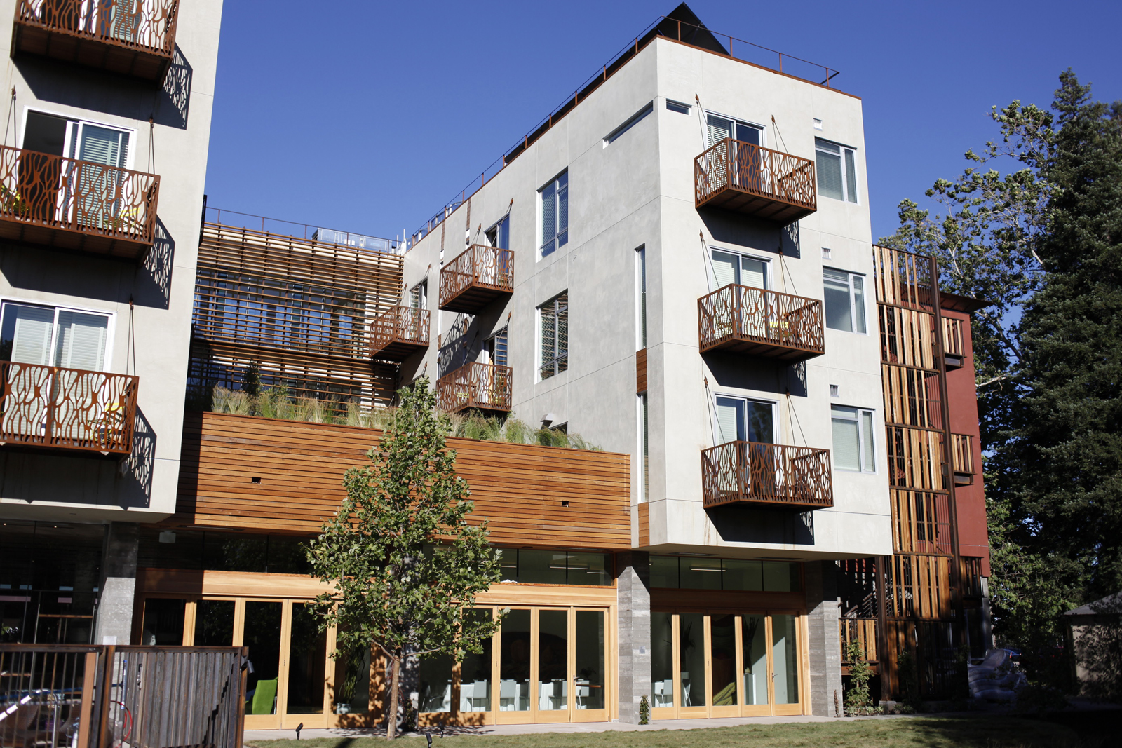 Here's the exterior of the hotel. Rusted balconies made of waterjet-cut Corten steel will gradually oxidize the surface of the walls. The shade screens on the stair and bridge are made of local, sustainably harvested redwood. Forty-five feet of sliding gl