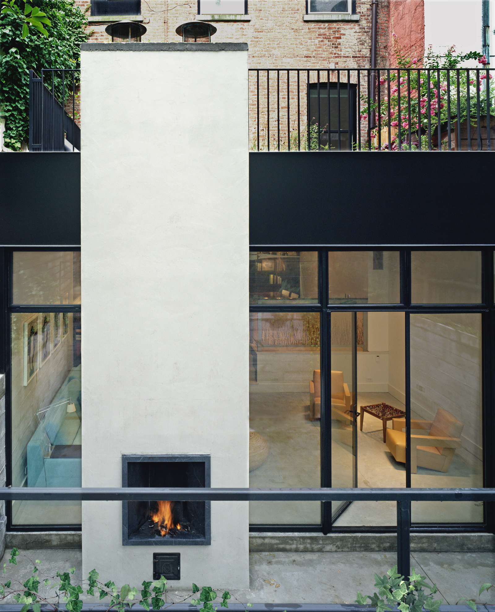 A chimney with back-to-back indoor and outdoor fireplaces anchors the steel and glass wall of the rear addition and allows the courtyard to be used well into autumn as an extension of the living space. Running the same troweled concrete flooring inside an