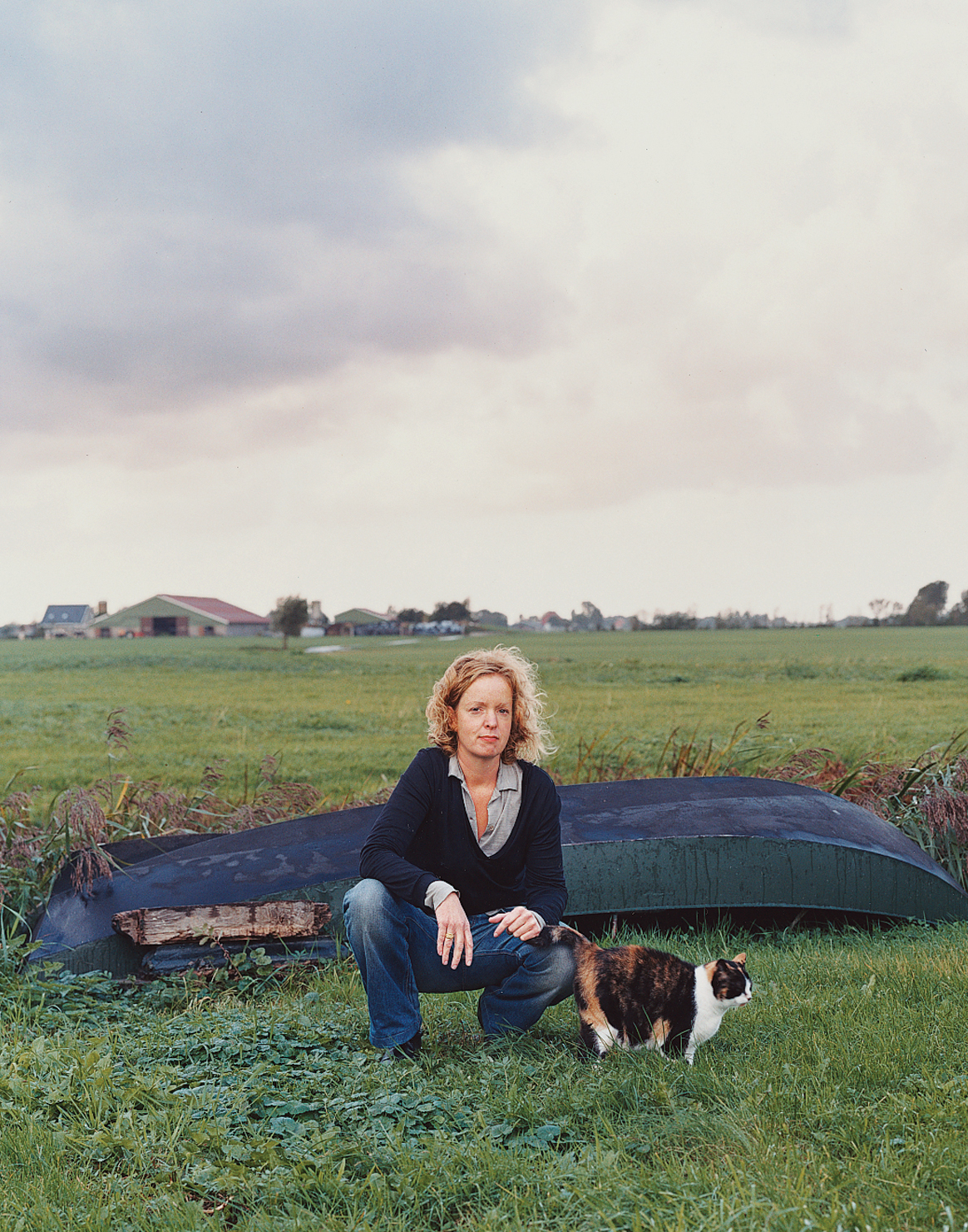 Claudy Jongstra kneels with a family cat in the yard behind her office and home, which she shares with her partner, Claudia Busson, and their two sons, Eabal and Jesk. Behind her is a small dinghy that the family uses to navigate the numerous irrigation c