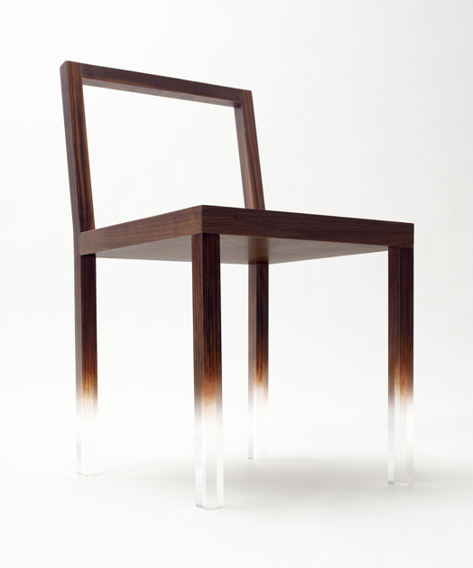 "The ""Fade-Out"" chair, a simple rectangular chair made from clear acrylic and painted with trompe l'oeil wood grain over most of the structure. The pattern fades away on the lower part of the chair legs to create the impression that the chairs are floating"