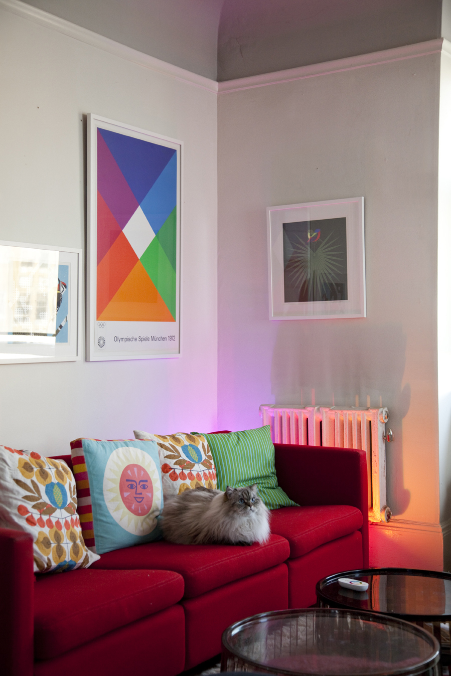 "In the living room, the <a href=""http://www.coloryourworldsweeps.com"">LivingColors</a> lamp, though obscured from view by a Knoll sofa by Charles Pfister, mimics the bright warm tones of the Max Bill poster. Grawe's cat, Eero, settles in amongst a collect"
