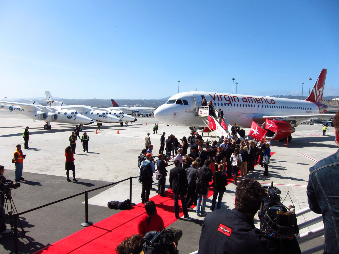 Virgin America is welcomed to its new home at SFO's Terminal 2 by Virgin Galactic's <i>WhiteKnightTwo</i> and a gaggle of press.
