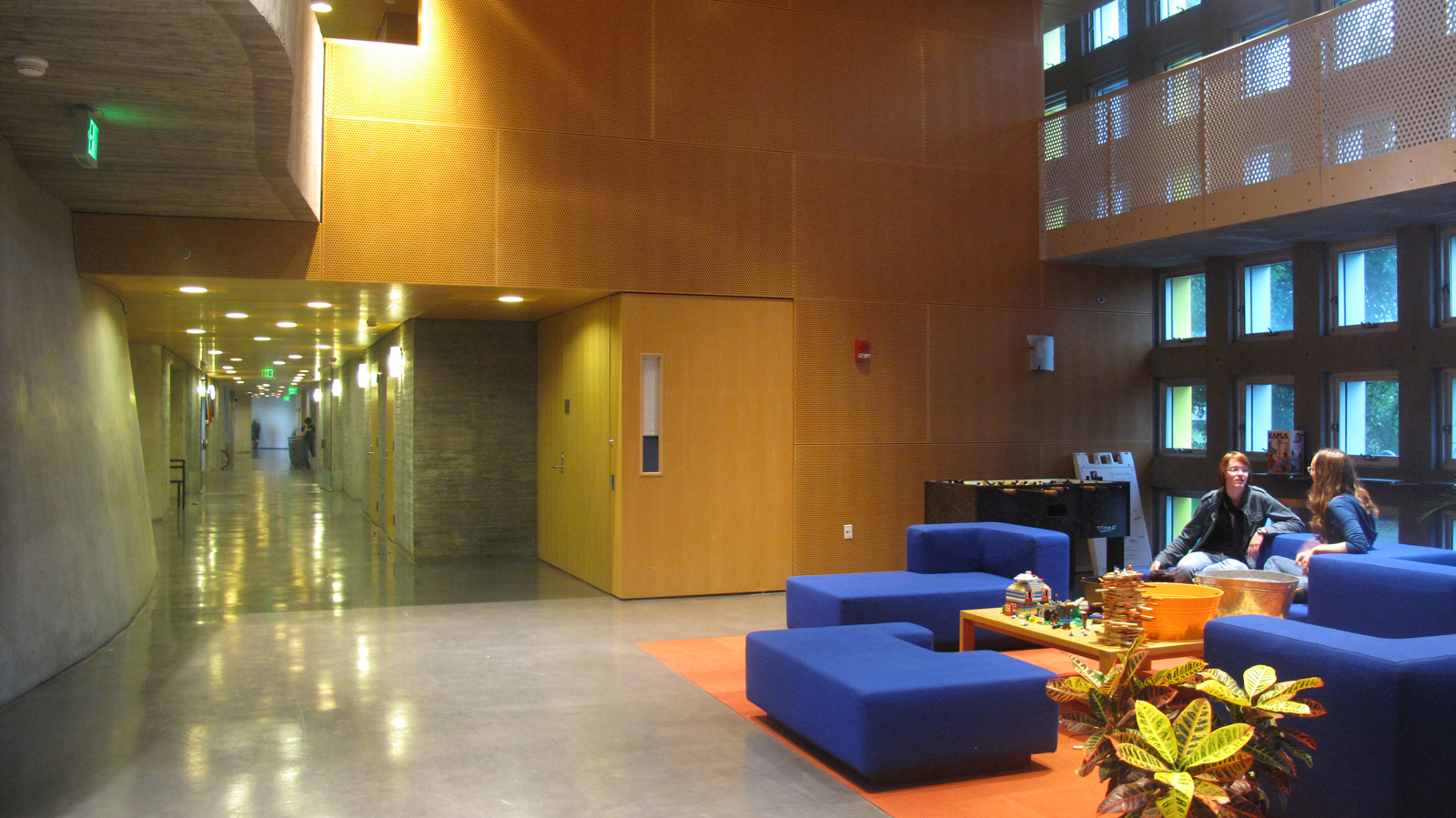 Renee and Amanda chat in the Simmons mail room, which is also the lobby and used as a meeting place. You can see three levels of porosity -- perforated wood paneling, metal overhead railing, and windows in the concrete walls.