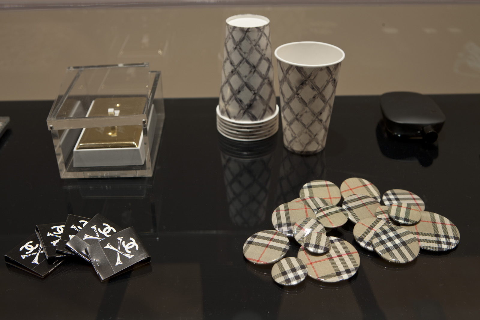 Another selection of objects on display including <i>Unauthorized Burberry Buttons</i> (1999). Burberry took to Wong's shenanigans and used the pins in one of their advertising campaigns. Photo courtesy SFMOMA.