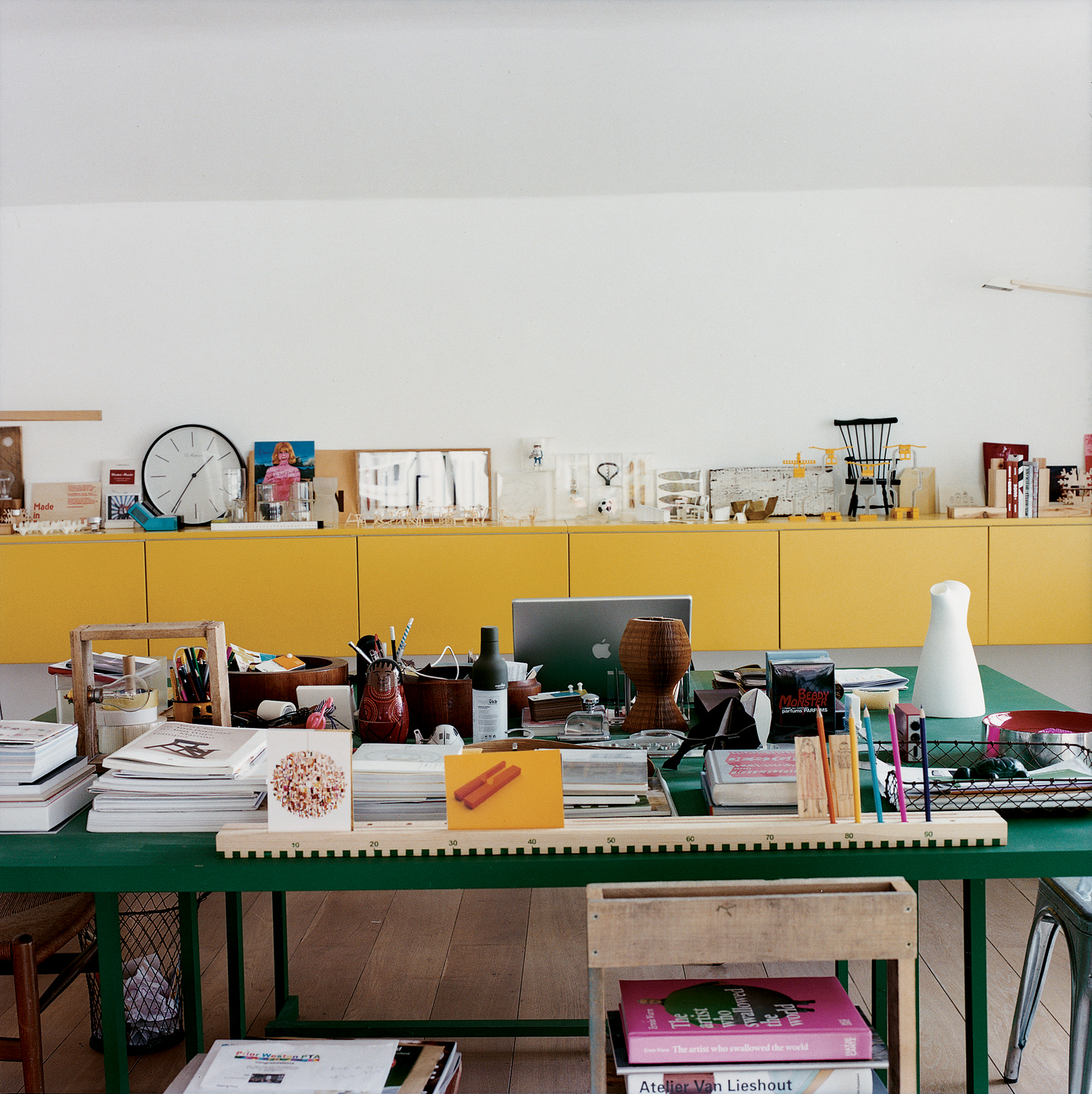 Behind Nina Tolstrup's dining table/office desk is a sideboard she designed herself, which is littered with things she has both collected and made.