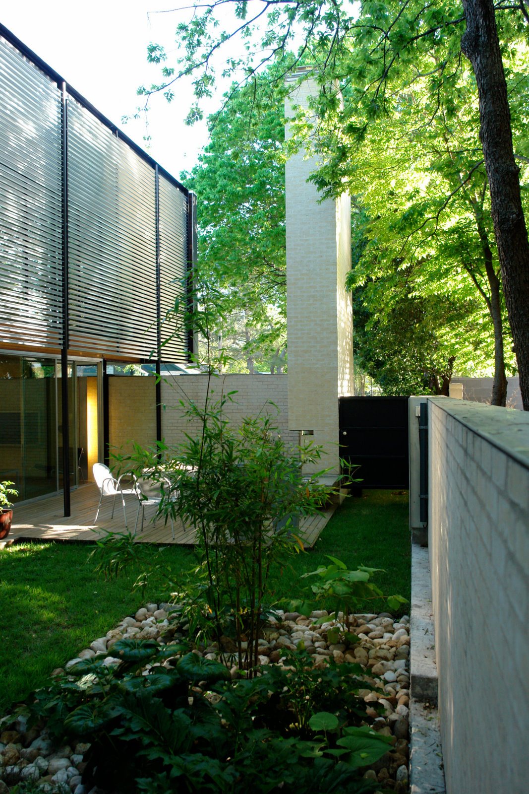 Along the entire west side of the house, a lush courtyard creates private exterior space that can be enjoyed during much of the year in Austin, particularly with large shade trees overhead. The entire ground level of the house opens onto the courtyard, in