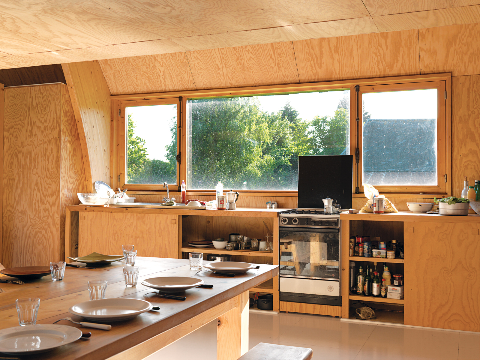 """In his kitchen built on the cheap, Barache installed appliances donated by a few architectural Good Samaritans. """"I don't even remember where the sink is from,"""" he says. Two built-in sliding-door cabinets house the kitchen basics, and the custom-built dini"""