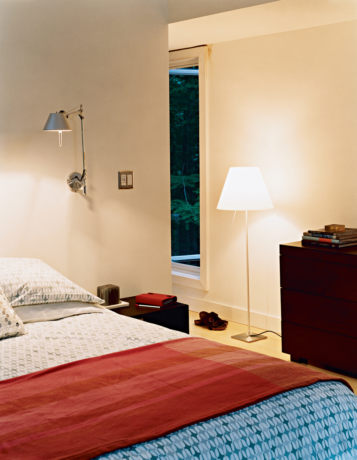 The master bedroom has a number of windows in varying shapes and sizes, providing unique views to the woods outside. The bed, chest of drawers, side tables, and geometric linens are all from West Elm. The Tolomeo wall lamps are by Artemide.