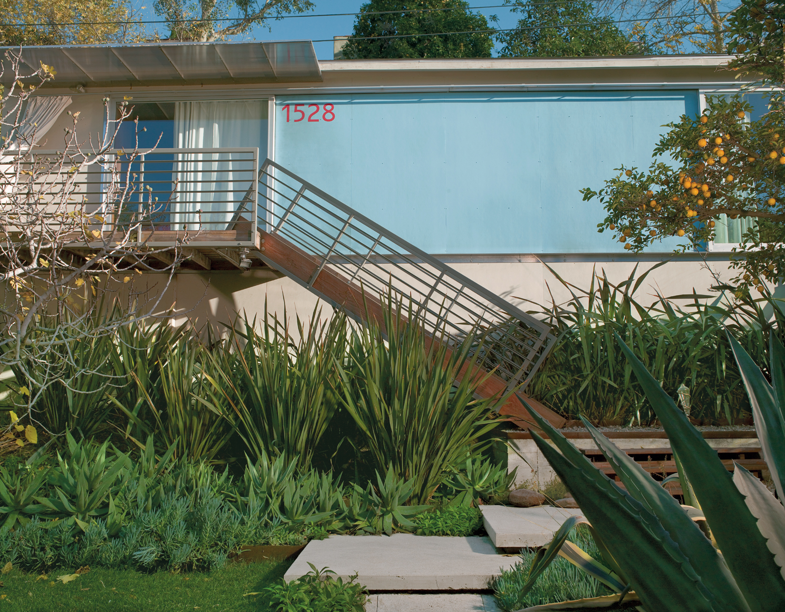 """Good Idea Studio redesigned the front facade with a welded tube steel staircase, an aluminum-and-polycarbonate awning, and fiber cement-board paneling painted """"Pool Party"""" blue."""