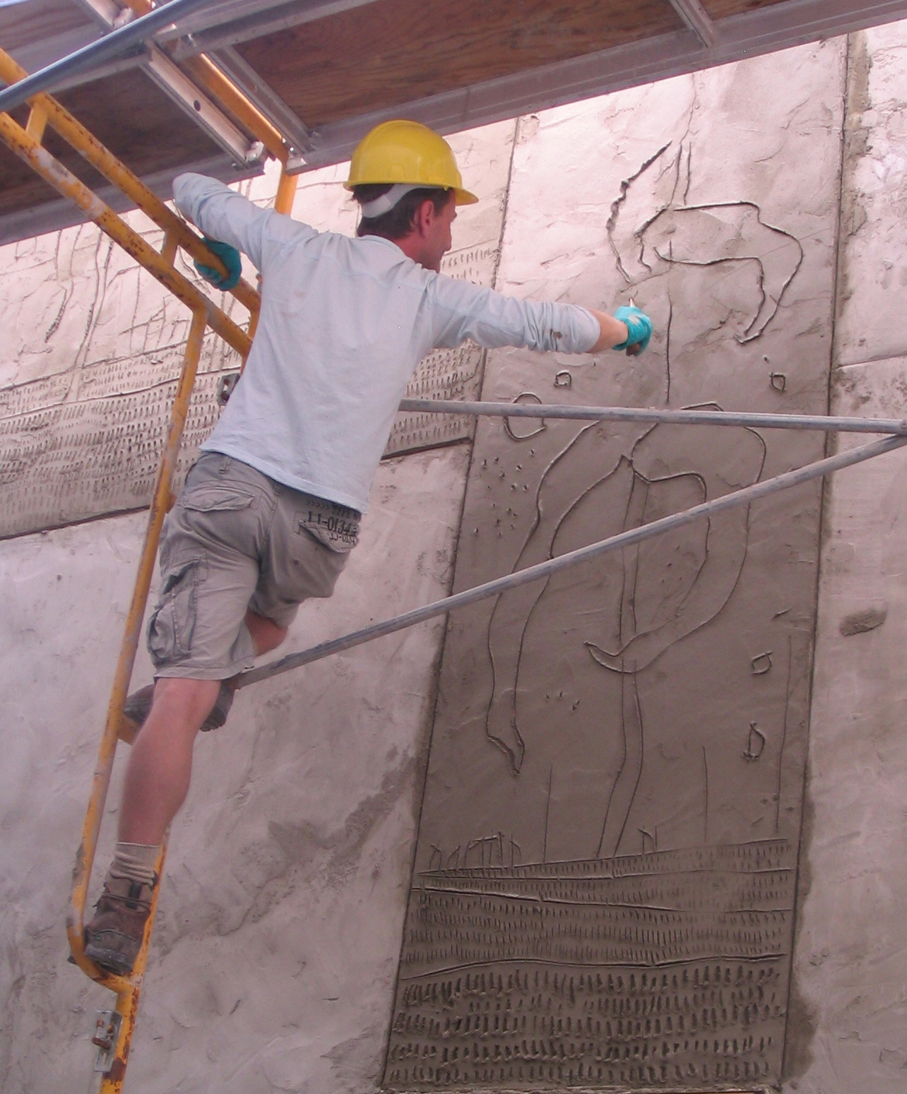 Griffin carves an exterior panel using a casuary bird femur bone knife—a dedication to early artistic tools and methods. Each panel received a fresh topcoat of concrete, after which the artist had no more than 15 minutes to make his marks before his canva