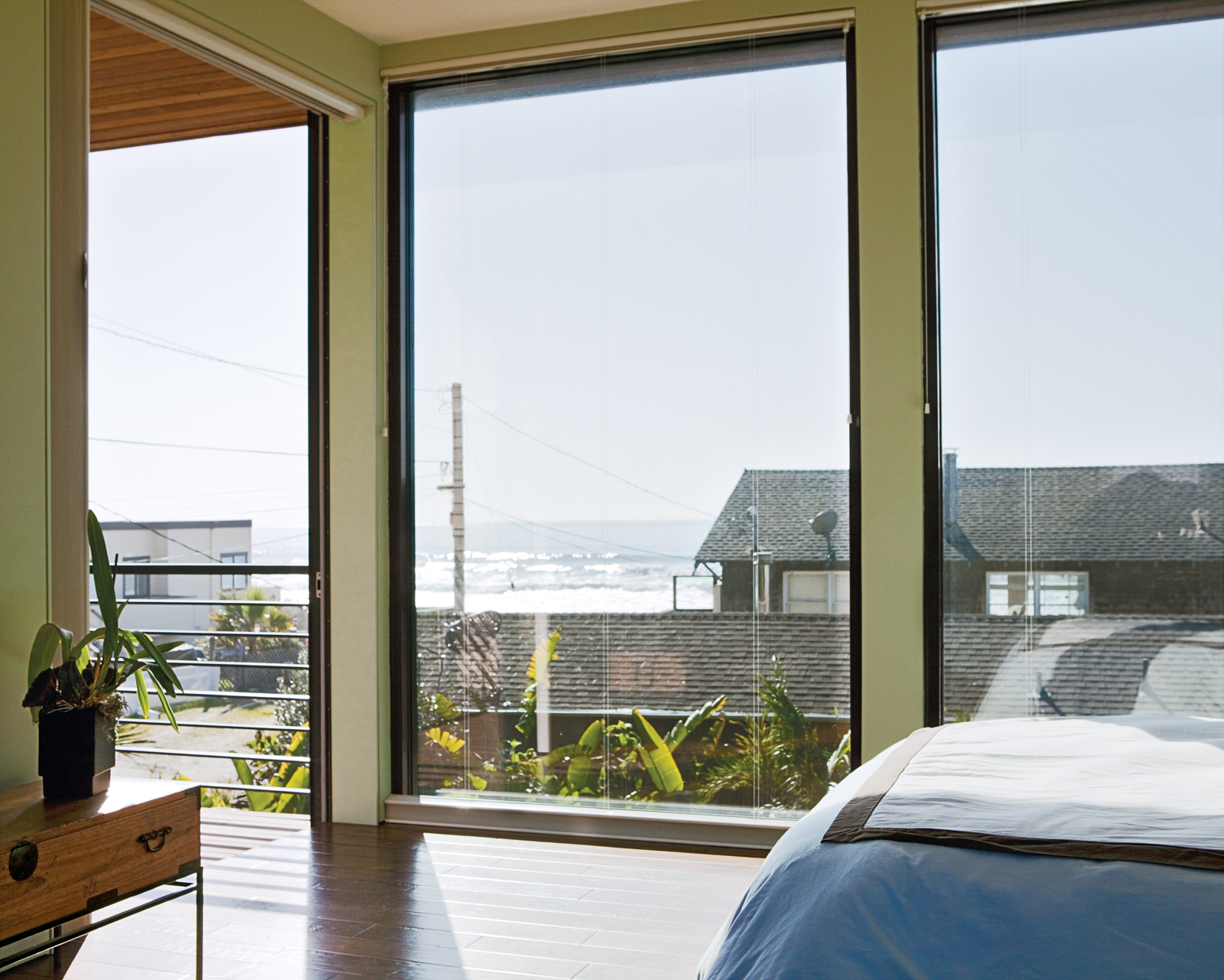 Floor-to-ceiling windows in the bedroom create the sensation of being outside, as if the entire house is one platform deck strategically shielded from the elements.