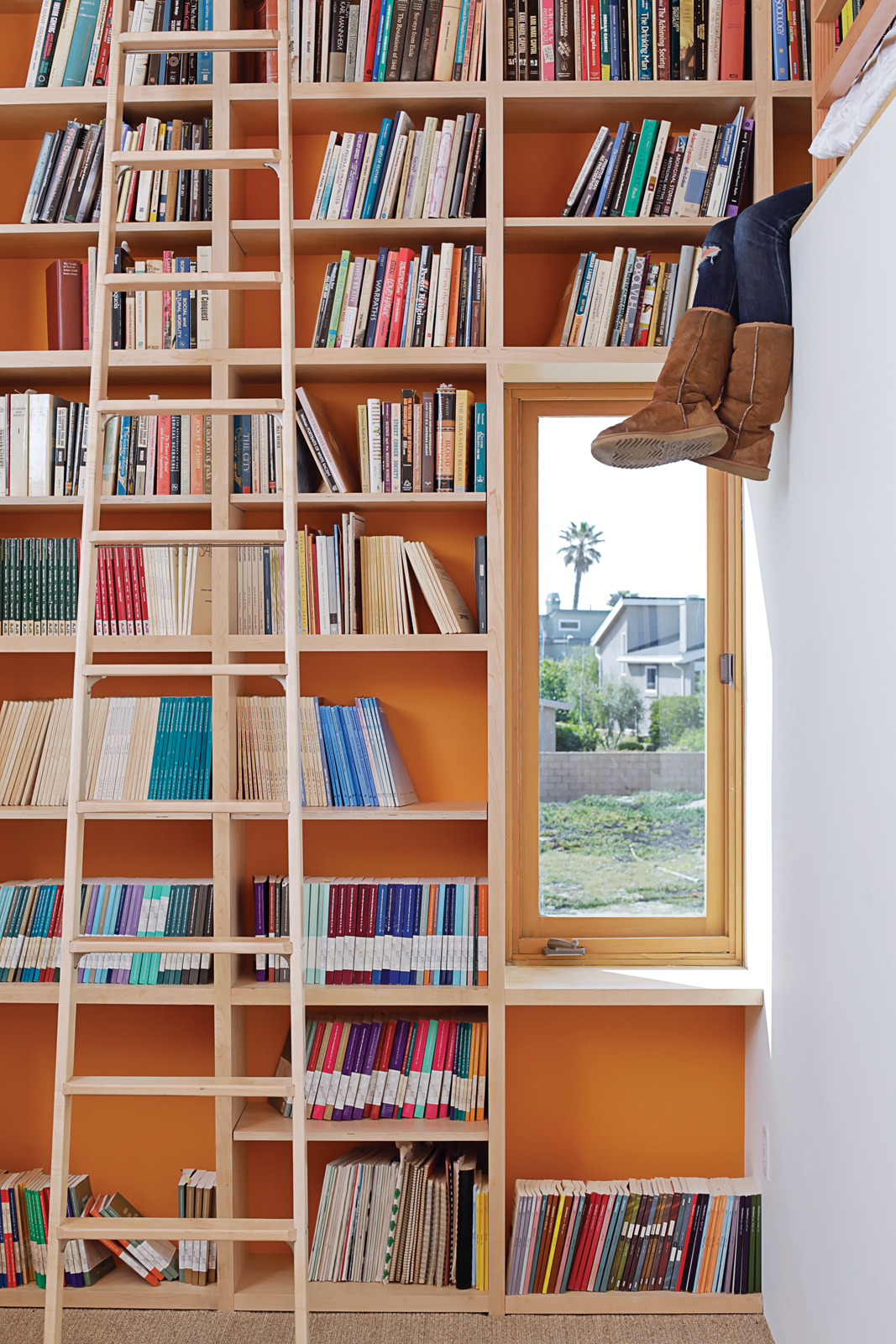 To make the most of 13-foot-high ceilings that help draw hot air out through second-floor windows and doors, designer Daniel Garness painted select walls with playful color and lined them with maple plywood bookcases. Library ladders (about $1,500 each fr