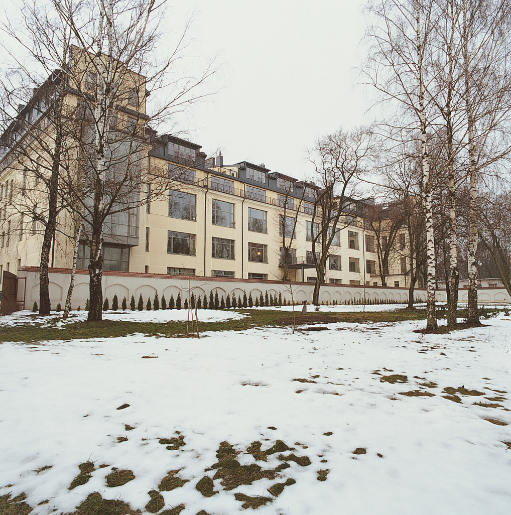 The renovated façade of Mikulionis's flat, seen beyond thin snow and bare trees from the grounds of the monastery.