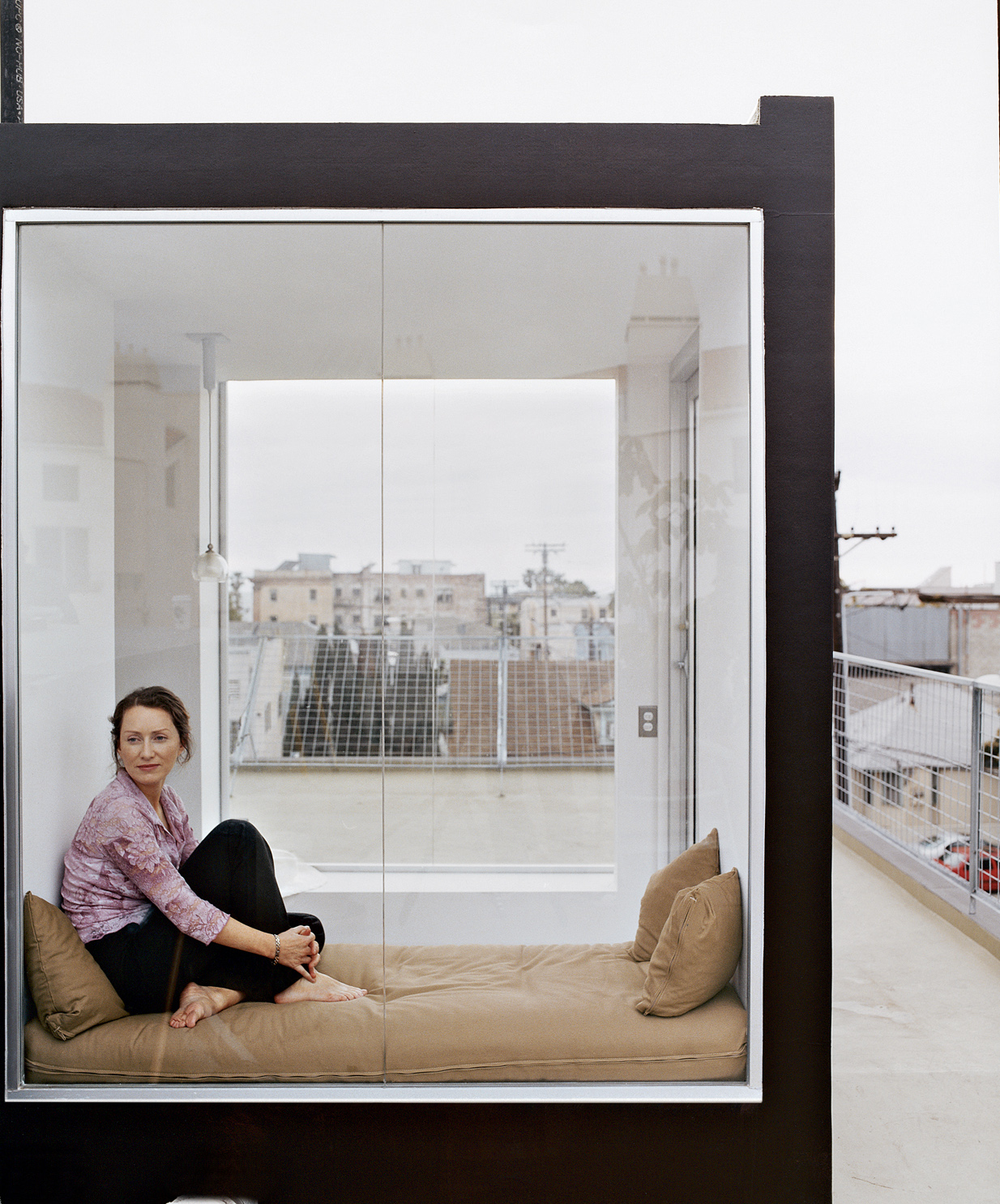 Irish-born actress Cornelia Hayes-O'Herlihy gazes across the Venetian roofscape. Her cozy glass enclosure rests atop the new home designed by her husband.