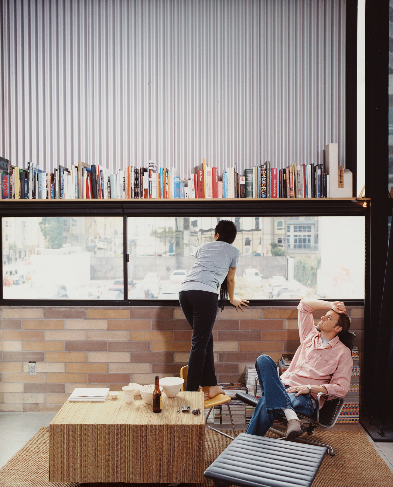 """The Schaffer's furniture includes an Eames Aluminum Group lounge chair (""""and ottoman!"""" adds Im.) A coffee table made of glued, corrugated cardboard was the couple's first project together, when they met in college eight years ago."""