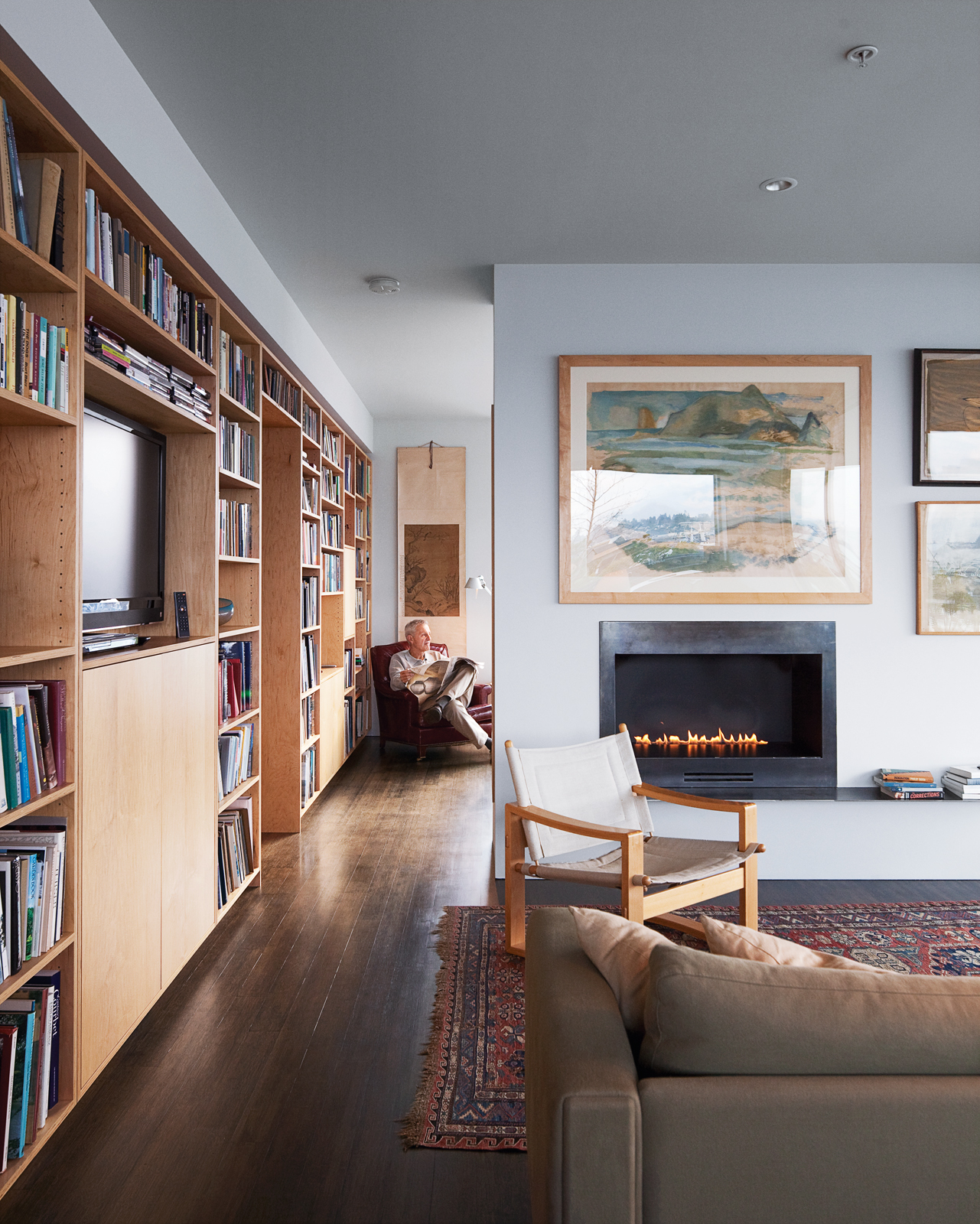 Bayley's ventless fireplace from Spark Modern Fires keeps the house toasty as he reads in his favorite red armchair, a vintage-store find, in his bedroom.