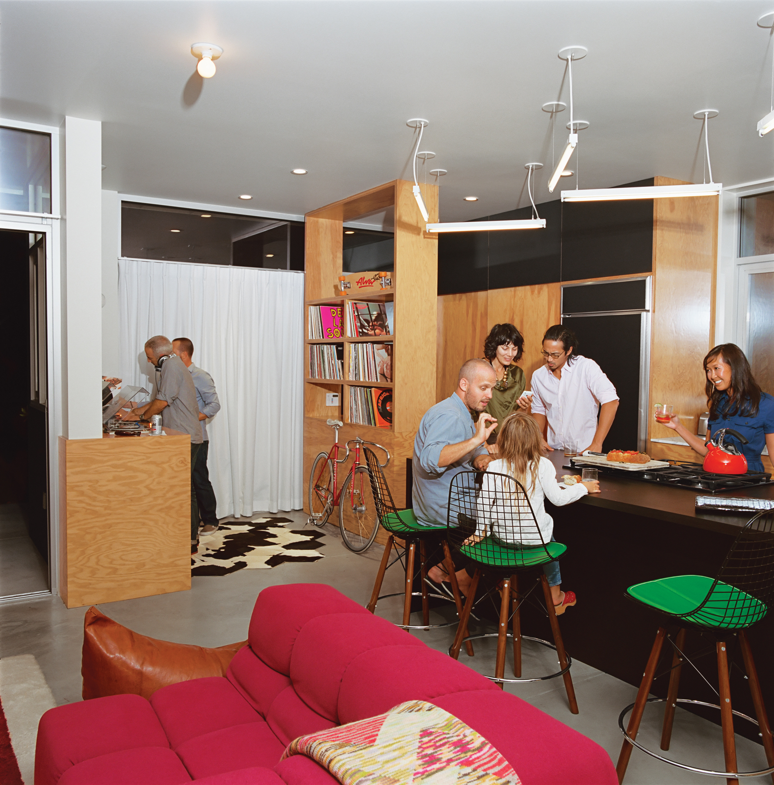 A music and cycling fan (the vintage bike is by Vivalo), Grunbaum mans the turntables while friends gather in the kitchen. Case Study barstools are from Modernica.