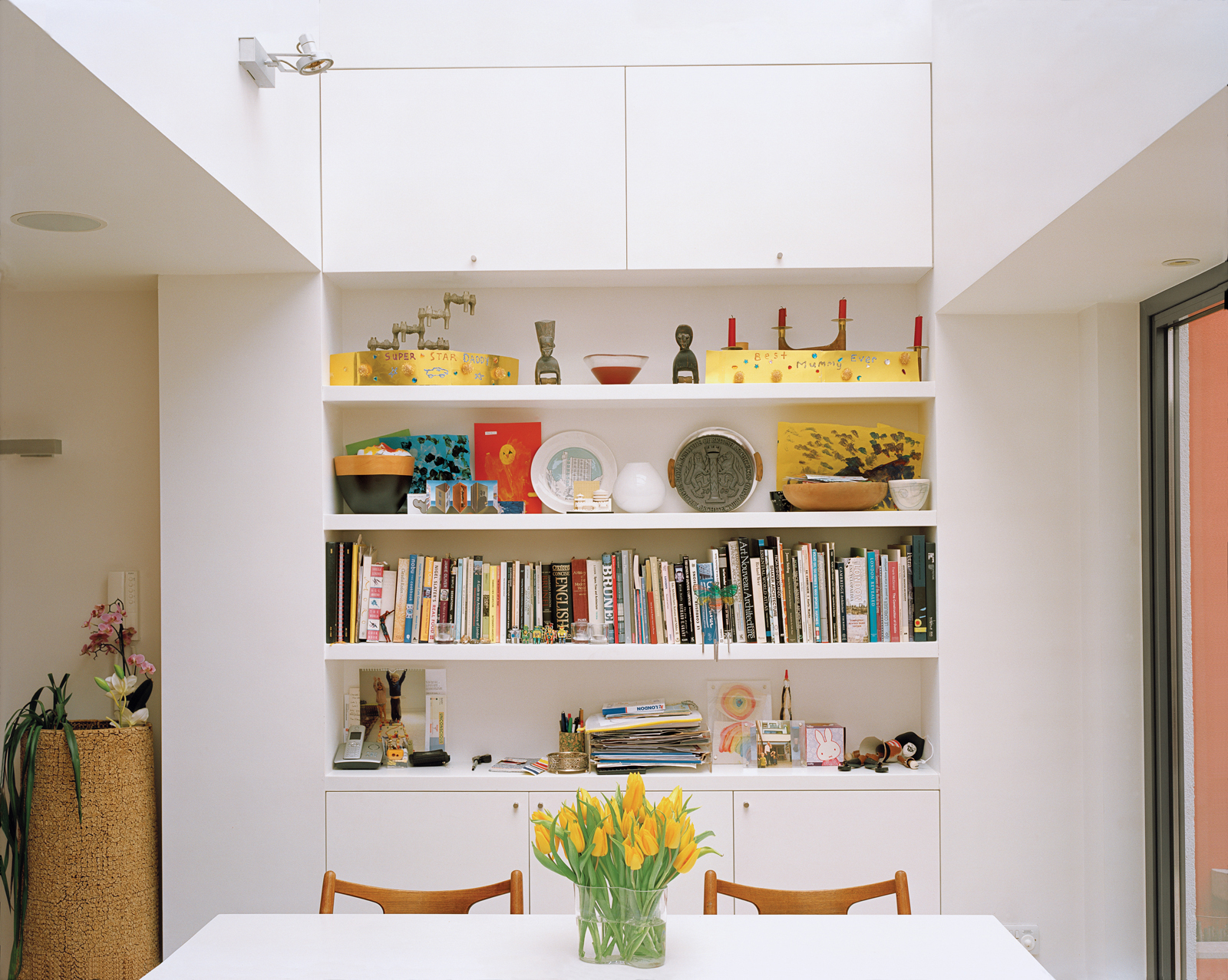 Throughout the house, built-in storage and shelving is cleverly positioned in alcoves and recesses, as in the dining area, which allows clutter to be easily cleared away.