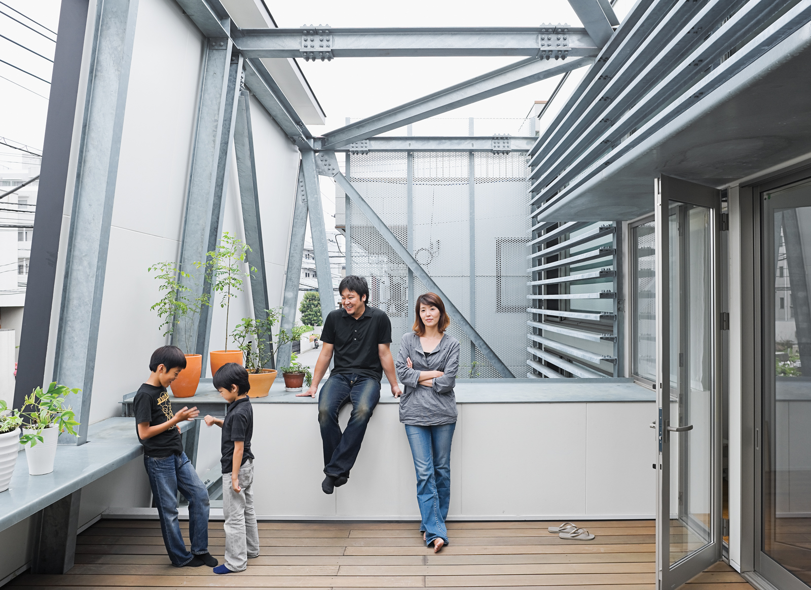 Slotted between the street-side enclosure and the living area is a breezy second-floor terrace. Brise soleil slats shade the interior. Yatabe's steel fabrication company created the robust, trusslike armature that extends from the house to support the dec