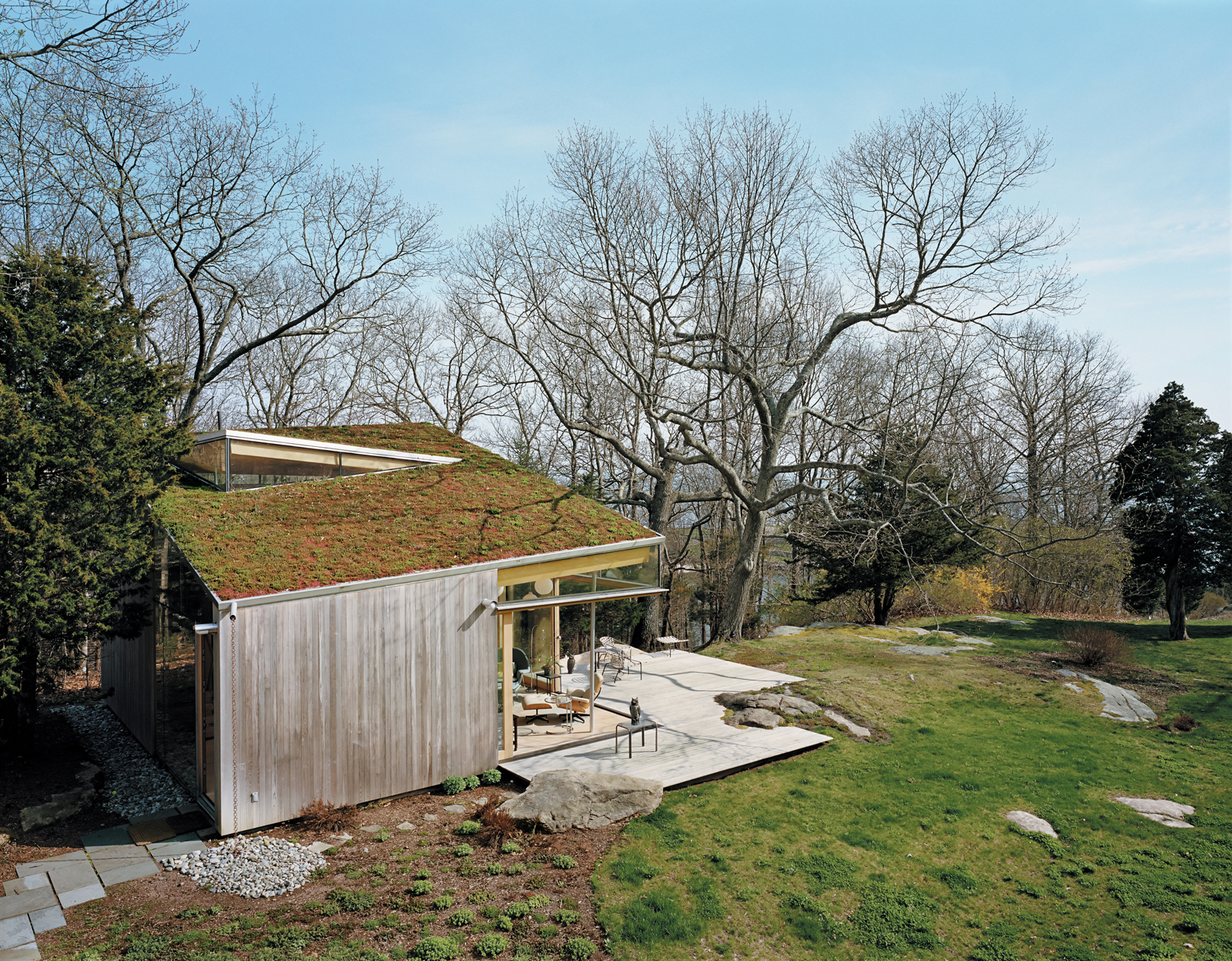 The deck, fashioned from ipe, was built around one of the property's many granite outcroppings. An earthen roof was planted with the same varieties of sedum that were added to the front of the cottage.