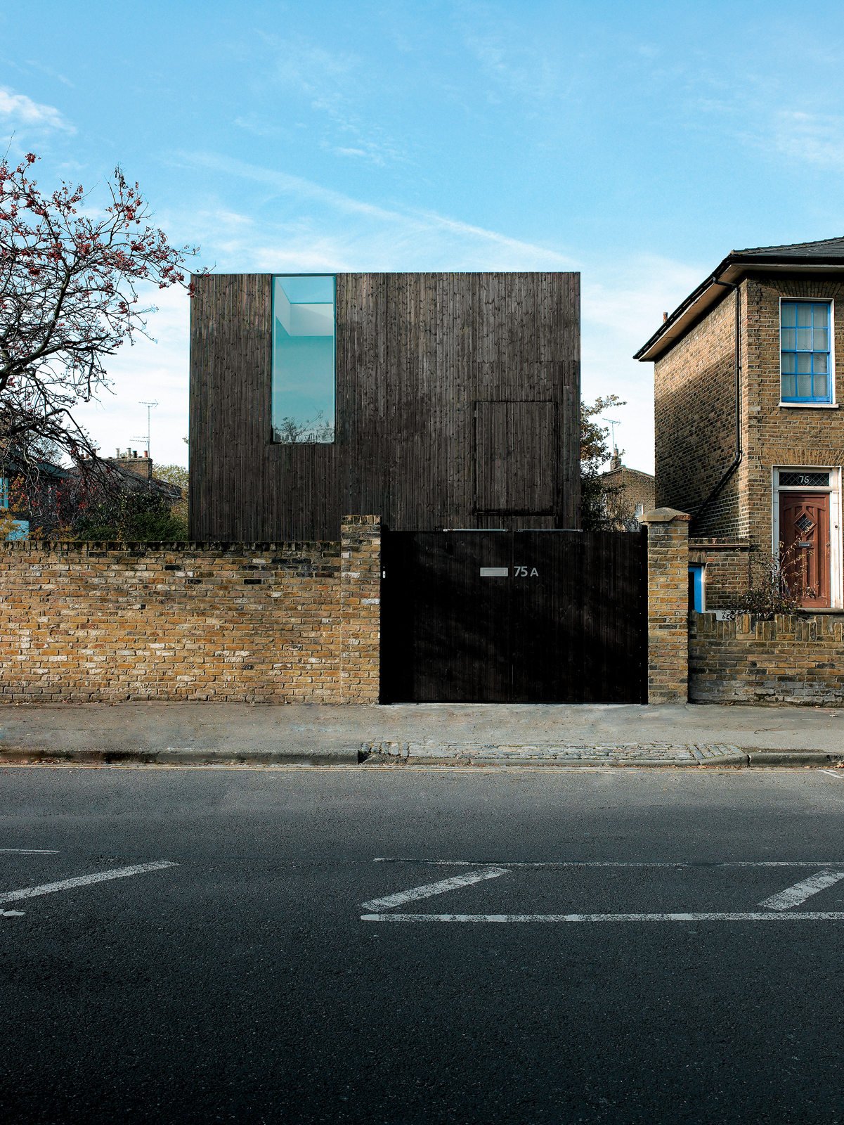 The facade achieves a notable sense of verticality for such a stout structure, with its stained-timber cladding aimed straight up toward the sky. The heavy, horizontal brick-work of the neighboring Georgian houses seems to imply aesthetic controversy, but