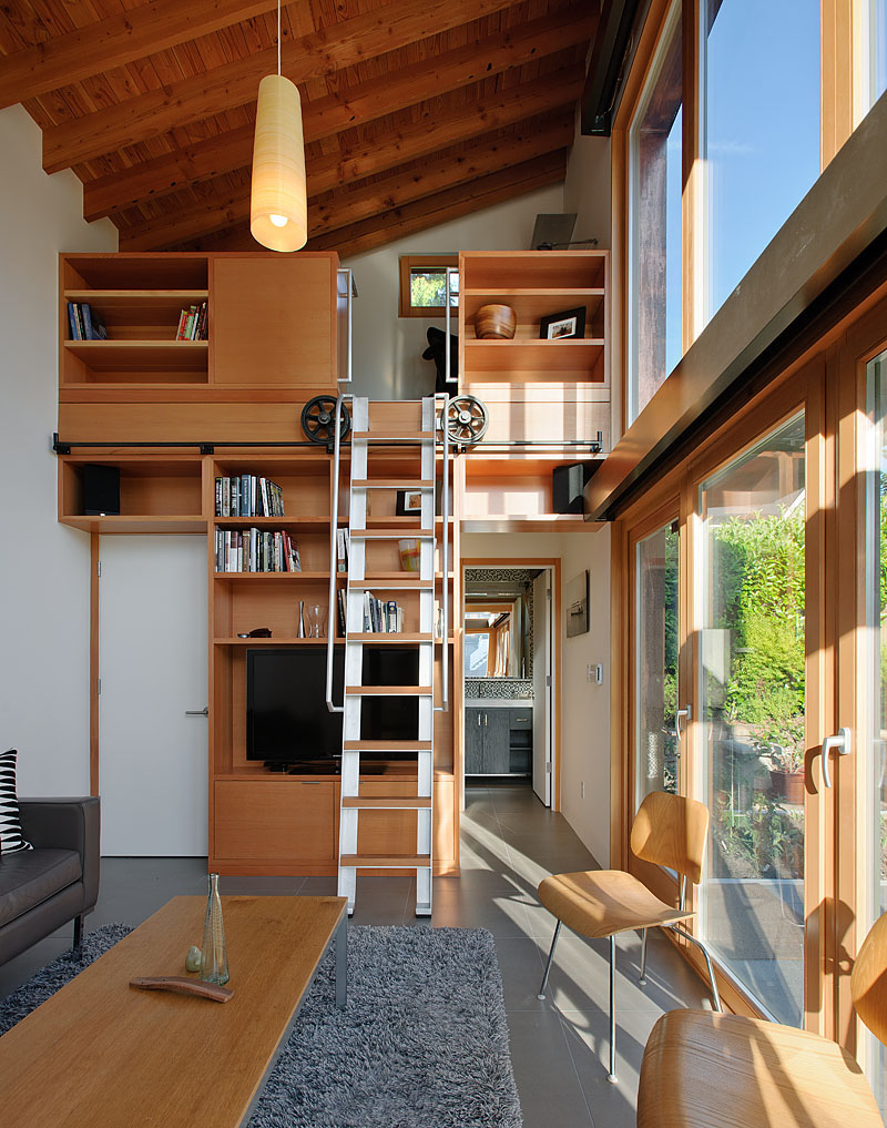 A rolling ladder made from salvaged wood and components leads to a small, yet well equipped, office.