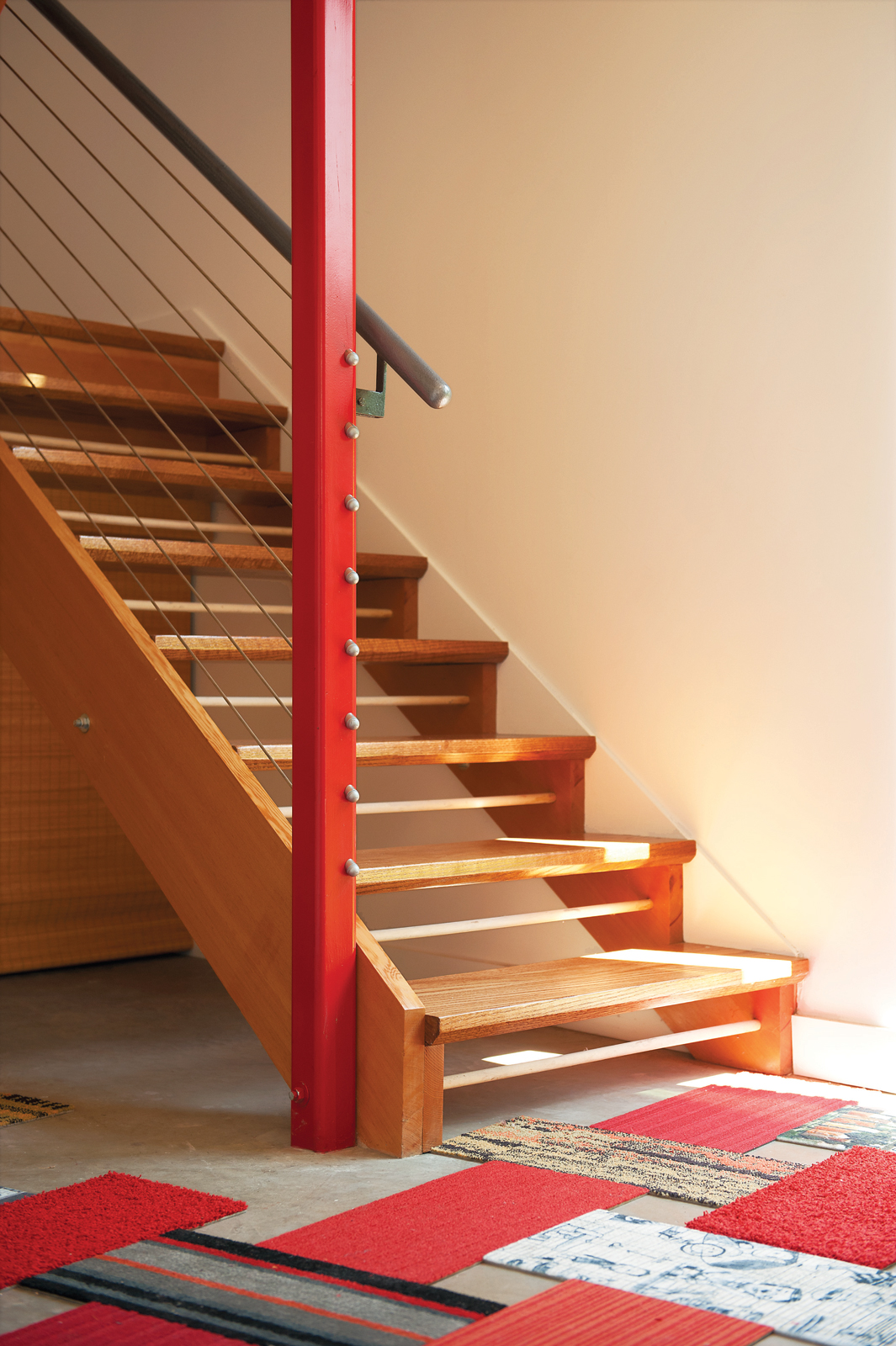 Wooden staircase with painted red pillar