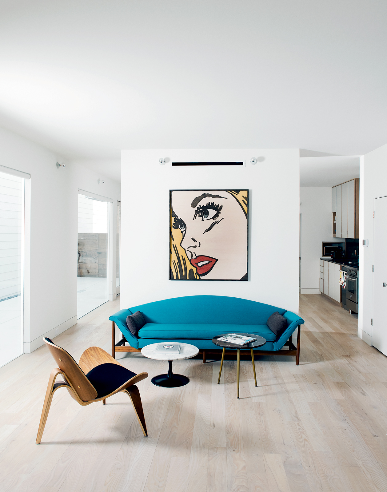 Modern living room with blue curved sofa and Mitch McGee print