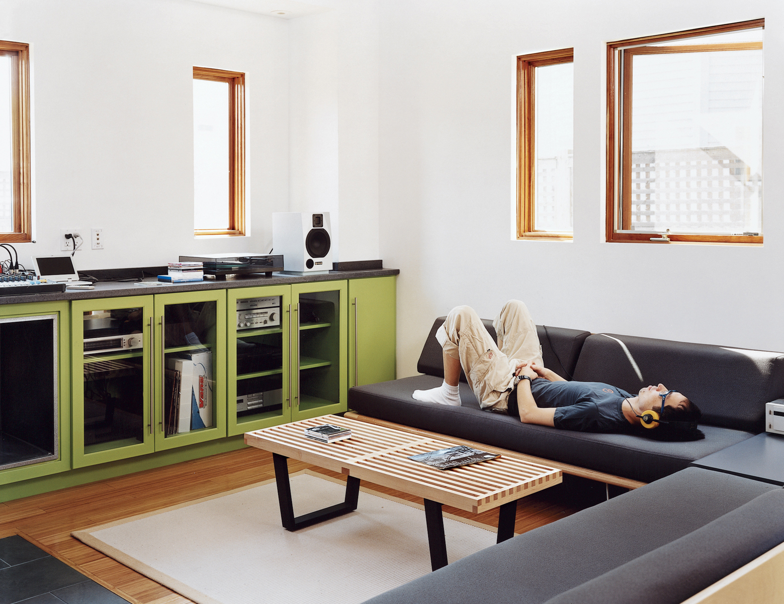 """Andy Hong tunes out with his hi-fi system in the living area of his ground floor. The big room contains a kitchen, a washer-dryer, and ample work surfaces. """"Since I travel a lot,"""" he says, """"I really look forward to hanging out in the big room, catching up"""