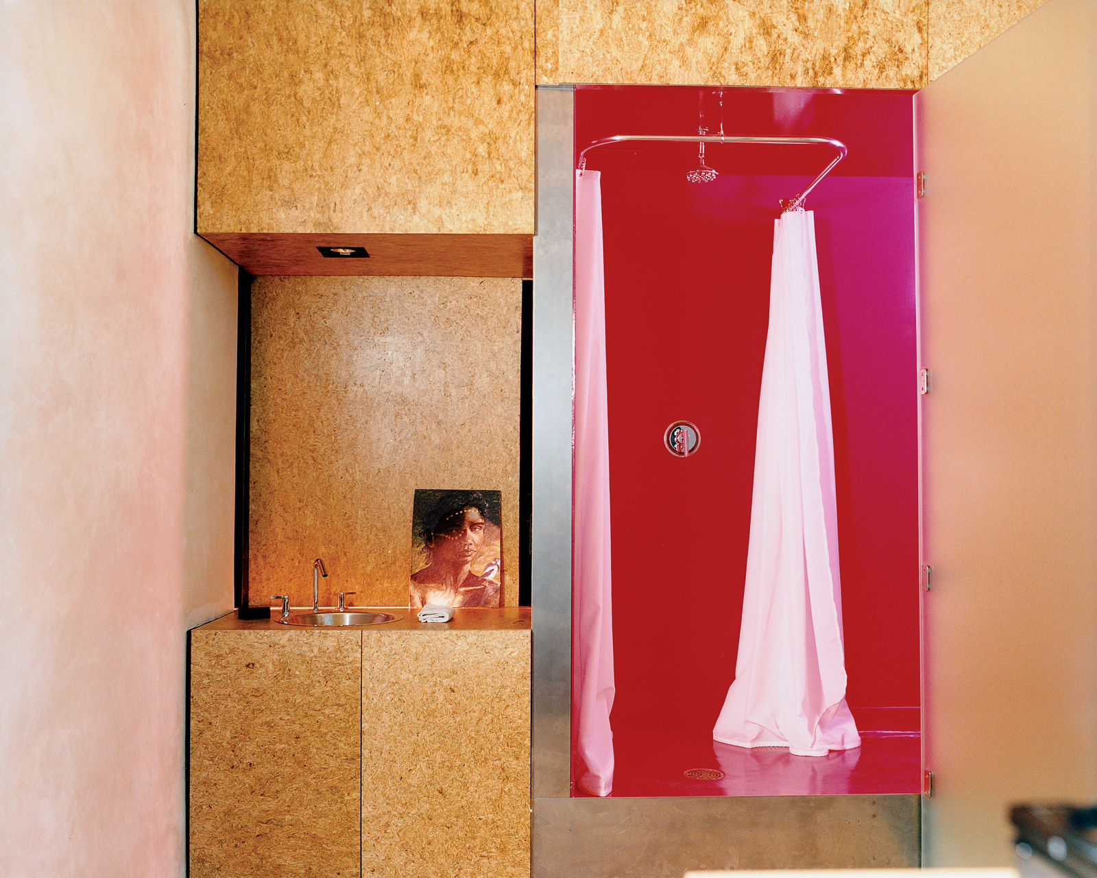 The Trzebiatowskis' bathroom retains the spirit of Arizona heat with its shocking magenta ceilings, floors, and walls. The vanity is anything but—opting for art instead of a mounted mirror—and is made from sanded and sealed oriented strand board (OSB), a