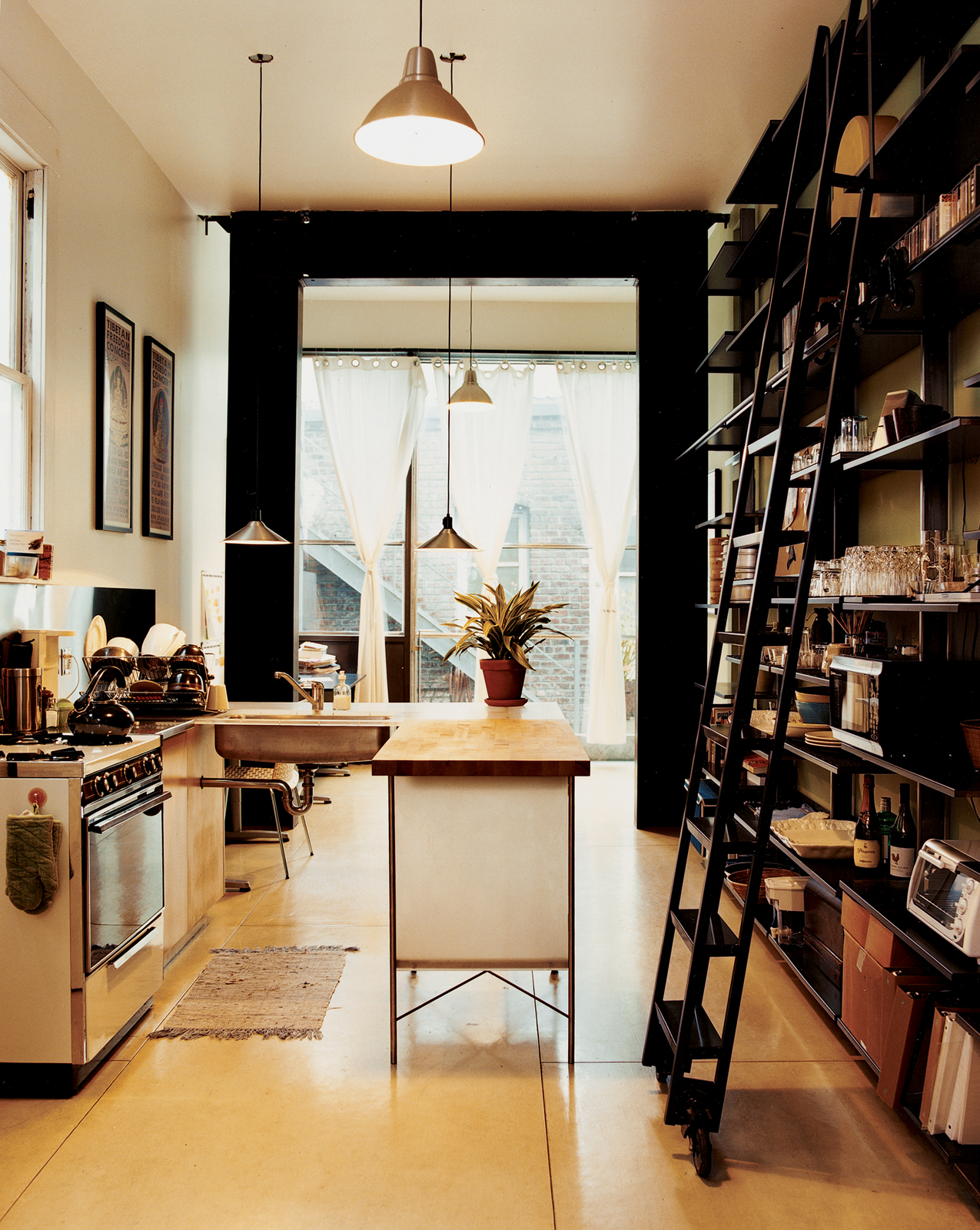Now rented out as an office/retail space, the downstairs contains a kitchen, which is fitted with Ikea lamps and steel shelving by Azevedo. For the flooring she glued down fiber-cement HardiePanel siding more commonly used for building walls, both because