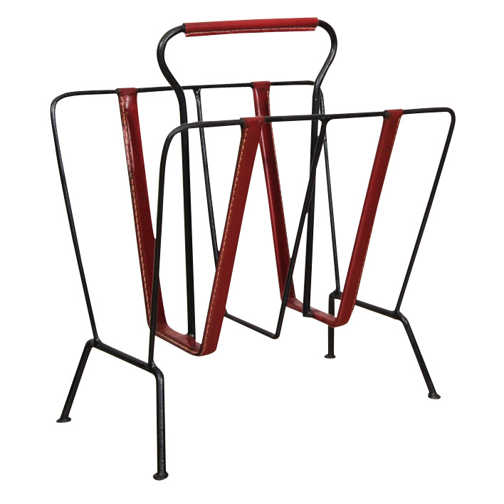 French designer Jacques Adnet (1904–1984) was particularly well known for his deft incorporation of leather elements into his furniture pieces. This rack, created sometime in the 1950s, is constructed of patinated wrought iron and delicately stitched red