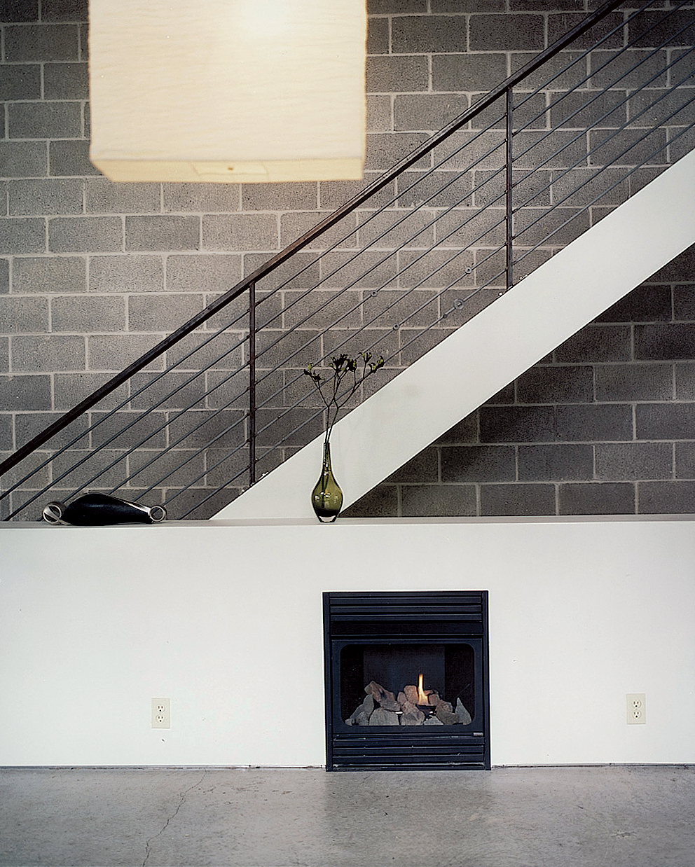 Still life with IKEA lampshade and ventless fireplace. The unfinished, black, welded- steel railing borders steps made of framing lumber, which emit a friendly, old-fashioned creak as Walz treads up and down.
