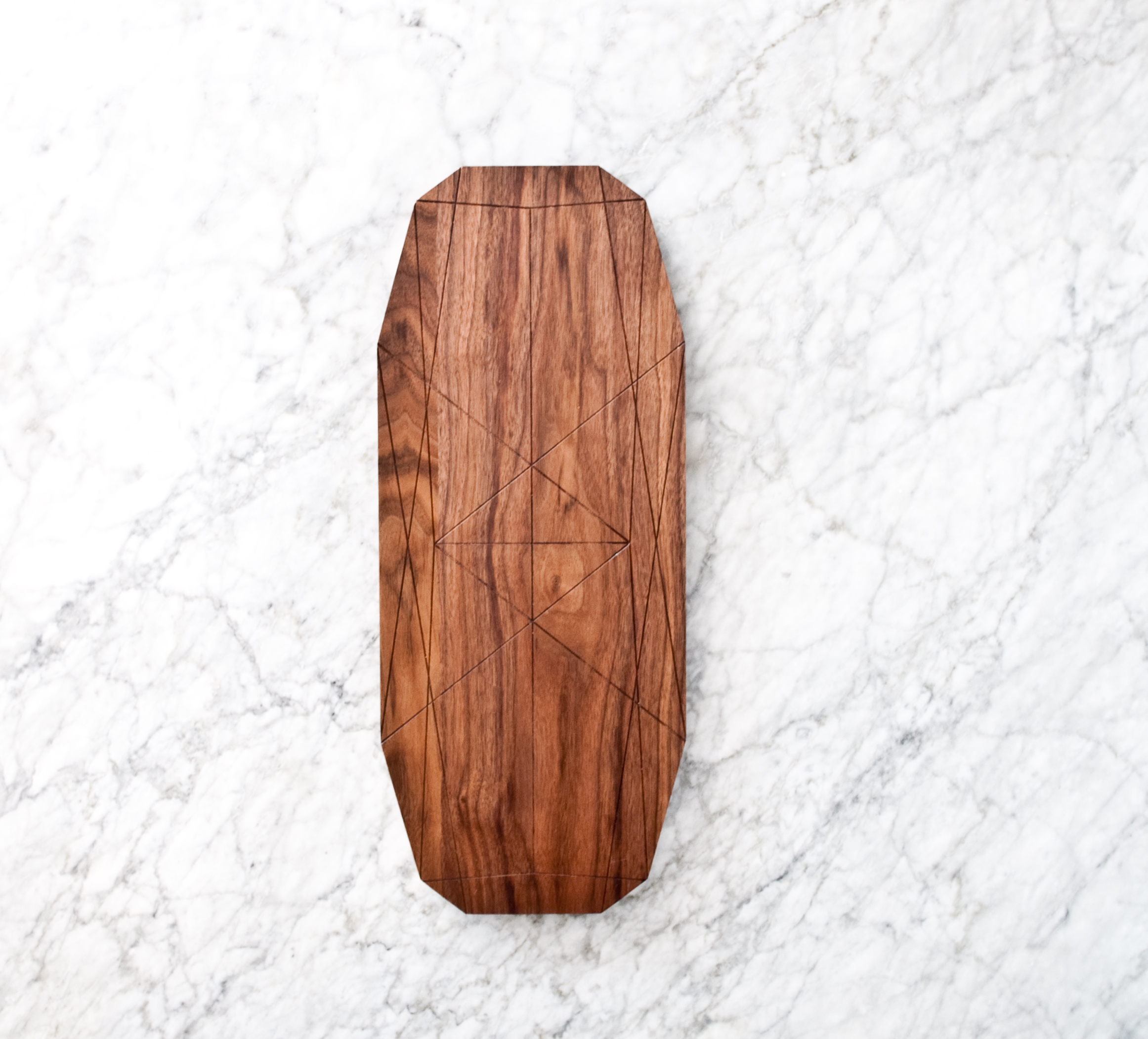 Long serving board crafted in rich walnut with geometric etchings